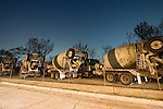Relaxing for the night, a row of cement mixer trucks are lined up awaiting duty the next morning, delivering cement to construction sites around the region.