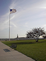 Flag flying over Lady Liberty on the horizon.