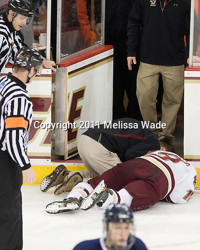 Bert Lenz (BC - Dir-Sports Medicine) tends to Chris Kreider (BC - 19) who was struck in the jaw (broken) by a puck. - The Boston College Eagles defeated the visiting University of New Hampshire Wildcats 4-0 while celebrating senior night on Friday, March 4, 2011, at Conte Forum in Chestnut Hill, Massachusetts.
