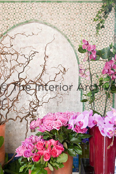 Close up of pink roses and orchids with wooden twisted branches