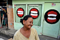 A woman trying hard not to smile and expose her less-than-pearly-white teeth, in front of a well advertised dental practice near the main port area of Ambon City. The 1999-2002 religious war between Maluku's Christian and Muslim populations, mainly centred on Ambon Island, led to over 5000 deaths and to around 500,000 people become displaced. Destroyed homes and offices, churches and mosques are slowly being either torn-down or renovated.  Urban centres, such as Ambon City, continue to be split along largely sectarian lines, and tensions are never far below the surface. Riots between Christian and Muslim youths erupted in September 2011 and, most recently, June 2012, though luckily simmered down just as quickly, partly due to community leaders learning how to defuse tensions from the earlier, more devastating, conflagration. /Felix Features