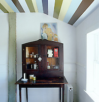 An antique wooden cabinet is placed on a table in a corner of the bathroom