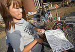 Miho Suzuki, 43, whose daughter Hana and son Kento were among the 74 Okawa elementary school students and 11 teachers who died or remain missing following the March 11 tsunami, shows a letter she has written to her children in front of a makeshift shrine outside the children's former school in Ishinomaki, Miyagi Prefecture, Japan on 07 Sept. 2011. Photograph: Robert Gilhooly