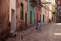 Woman walking down a sreeet lined with Spanish colonial houses in the city of Guanajuato, Mexico.