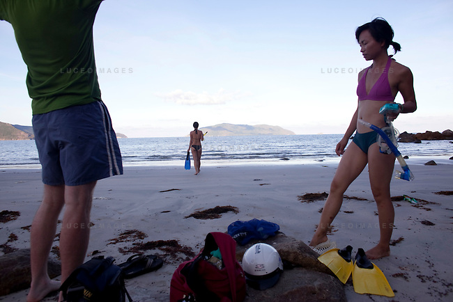 Julia Le, 35, right, and her boyfriend Mark Hartman, 34, of San Jose, Calif., get ready to go snorkeling at Bai Nhat beach on Con Son Island, part of the Con Dao Islands.The 16 mountainous islands and islets are situated about 143 miles southeast of Ho Chi Minh City in Vietnam, in the South China. Photo taken Thursday, May 5, 2010...Kevin German / LUCEO For the New York Times