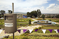 "Rwanda. Kigali province. Kigali. Downtown. Traffic circle in the town center. Water fountain.Public dustbin. Trash can means ""poubelle"". The small triangle flags, white and mallow, are for the 13th commemoration of the Genocide. Mauve is the color of mourning. © 2007 Didier Ruef"