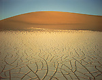 Mudcracks and Sand Dunes at twilight, Death Valley National Park, California