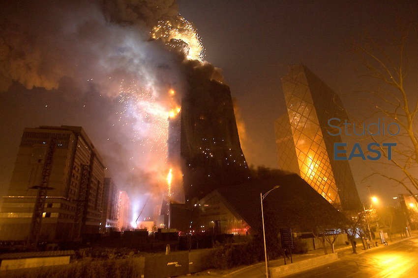 Fire rages through the under-construction Mandarin Oriental hotel, which is part of China Central Television's new headquarters complex in downtown Beijing, China, on February 9, 2009. Part of the iconic CCTV (China Central Television) complex, the building housing the Mandarin Oriental Hotel exploded after it caught on fire Monday, the last day of celebrations for the lunar new year when the city was alight with fireworks. The building was designed by the Dutch architect Rem Koolhaas and is part of CCTV's new headquarters, an angular wonder of modernist architecture that was built to coincide with the Beijing Olympics last year. The fire was burning from the ground floor to the top floor, the flames reflecting in the glass facade of the main CCTV tower next to the hotel and cultural center. The 241-room Mandarin Oriental hotel in the building was due to open this year. Photo by Stringer/Pictobank