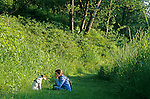 Jack Russell Terrier with young girl sitting along a trail