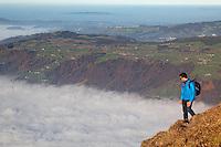 Man hiking above foggy valley from near summit of Mount Rigi, Bänderenweg route, Switzerland, Europe