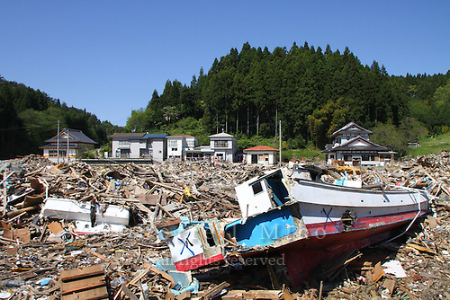 May 18, 2011; Minamisanriku, Miyagi Pref., Japan - 1.2 kilometers inland, a fishing boat sits amongst splintered wood and debris in the shadow of homes that were virtually untouched after the magnitude 9.0 Great East Japan Earthquake and Tsunami that devastated the Tohoku region of Japan on March 11, 2011.