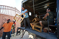 Andy Chaggar unloading newly constructed desks and benches for a home school at an orphanage supported by EDV, Port-au-Prince, Haiti. EDV is committed to affecting permanent change in disaster-affected communities worldwide. Their role is to facilitate personal connections between volunteers and the survivors of disasters.  The charity is based on a proven model developed by several landmark organisations that have paved the way for citizens to become disaster volunteers. These landmark organisations have shown that supposedly ordinary people working together with the guidance of knowledgeable leaders can make an extraordinary difference in the lives of those affected by disaster..EDV believe that to provide meaningful relief and reconstruction assistance to disaster affected communities they have to do more than reconstruct buildings. They need to understand and address the factors that made a community vulnerable to the disaster in the first place. The charity's work is organised with these factors in mind so that they can affect change that far outlives their presence..EDV believes that survivor motivation is essential to the recovery of any disaster-affected community. Their operations will always be predicated on the idea that survivors may be traumatised, but they are not helpless. With this in mind, EDV encourages host communities to direct their own recovery. EDV believe that this empowerment is essential in helping survivors feel a renewed sense of control over their lives which will, in turn, help overcome the feelings of hopelessness that can follow a disaster and inhibit long term recovery. EDV also believe that social cohesion is of primary importance in any disaster-affected area. No amount of bricks or mortar will bring about sustainable improvement if communities fail to come together or are disrupted by relief efforts. Therefore, their operations will always aim to foster communication and cooperation within and between the communities they serve.