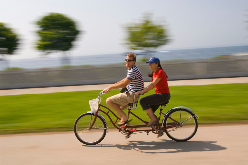 A couple rides a tandem bicycle around Mackinac Island in Michigan.