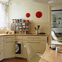A clever cabinet with drawers which hold spices cereals and grains stands on the kitchen counter