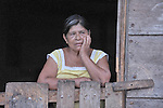 A woman in the doorway of her home in Las Flores, Ixcan, Guatemala.