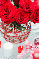 A vase of red roses forms the centrepiece of the dining table