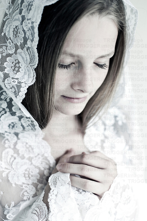 Female youth with sad expression wearing white lace veil
