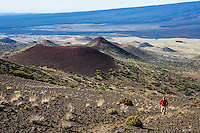A hiker on Mauna Kea Summit Trail, with a cinder cones (or pu'u) and the slope of Mauna Loa in the background, Hawai'i Island.