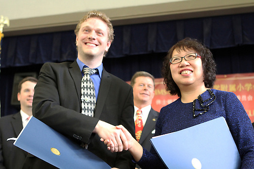 Bryan Bordelon (L) and Zheng Ruifang, shake hands following the signing of a Sister School Agreement between their campuses.