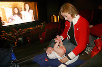"A young mother changes her son's nappy in the cinema. In specially organised ""baby-movie"" showings popular films are screened with lower volume and with space made available for pram parking..In contrast to most European countries, the Norwegian birth rate is a healthy 1.9. Norway's reputation as a child friendly society is partially founded on a succession of government initiatives to improve parents' rights and economic circumstances."
