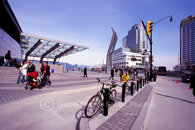 """Tourists walking along Plaza at the Entrance to the New Convention and Exhibition Centre Vancouver, British Columbia, Canada.  """"Canada Place"""" in Background."""