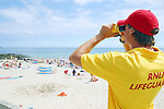 RNLI Lifeguard on patrol at Gyllynvase Beach, Falmouth, Cornwall, UK