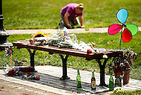 People gather around a memorial for actor and comedian Robin Williams in the Boston Public Garden at the bench where a scene from the movie 'Good Will Hunting' was filmed. Chalk writings, flowers, and memento's surround the bench the day following the death of Robin Williams at age 63. (Photo by Jared Wickerham/Wick Photography)