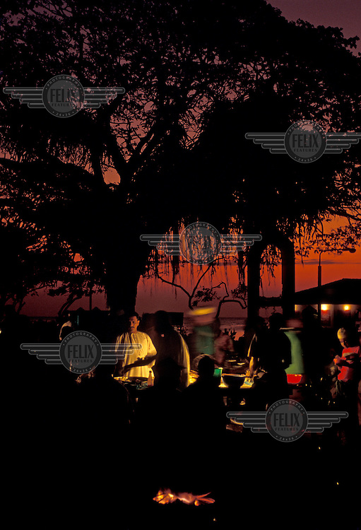 Foodstalls by the water front at dusk.