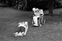 England London. Couple asleep. Husband and wife napping in Hide Park. A handicapped woman on a wheelchair and a man lying on a blanket on the grass. © 1992 Didier Ruef