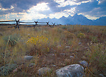 Wyoming, Rays of light stream over the Teton Range in autumn with a rustic log fence.
