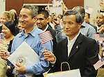 Braulio Ramon, left, and Shengkun Wen wave U.S. flags after becoming United States citizens during a naturalization ceremony in federal court in Oxford, Miss. on Friday, June 29, 2012. Forty seven persons took the oath of citizenship. (AP Photo/Oxford Eagle, Bruce Newman)