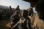 Afghan border police and soldiers from Alpha Battery 3-321 Field Artillery watch rockets fired by US Kiowa helicopters strike Taliban positions during an attack on Border Security Post 7 in Afghanistan's eastern Khost Province on the Afghan-Pakistan border on Sunday Oct. 19, 2008.