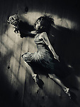 Young woman in a dress with a bouquet of wild flowers in a dynamic leap on wooden floor background, abstract artistic portrait in dramatic dim light black and white in vintage tones