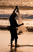 Fisherman holding net at sunset at Seminyak Beach in Bali, Indonesia