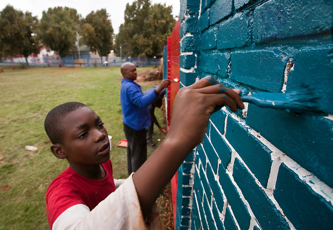 Mar. 15, 2012; Community members help paint a wall in Johannesburg, South Africa. Notre Dame Art & Design students painted the formerly graffiti-covered wall as part of the together+ campaign,  research and analysis project for design to actively change xenophobic beliefs and perceptions...Photo by Matt Cashore/University of Notre Dame