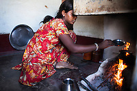 Nitu (not her real name), cooks in the kitchen in Jhaju village, Bikaner, Rajasthan, India on 4th October 2012. Now 18, she was married off at age 10 to a boy of around the same age, but only went to live with her in-laws when she was 12, after she had finished studying up to class 6. The three sisters, aged 10, 12, and 15 were married off on the same day by their maternal grandfather while their father was hospitalized. She was abused by her young husband and in-laws so her father took her back after hearing that her husband, who works in a brick kiln, was an alcoholic and was doing drugs and crime. She had only spent a few days at her husband's house at that time. Her father (now out of the hospital) has said that she will only be allowed to return to her husband's house if he changes his ways but so far, the negotiations are still underway. Photo by Suzanne Lee for PLAN UK