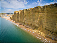 BNPS.co.uk (01202 558833)<br /> Pic: JamesLoveridge/BNPS<br /> <br /> Holidaymakers risk their lives by posing for pictures on one of the rockfalls under the famous cliffs at West Bay in Dorset yesterday.<br /> <br /> The dangerous site, made famous by the TV crime drama Broadchurch, claimed the life of a holidaymaker in a rockfall in 2012, and there are many signs warning visitors to stay away from the base of the towering cliffs.<br /> <br /> Photographer Graham Hunt was shocked to see the group line up for the picture and said 'I couldn't believe my eyes, sudden rockfalls are common and they were risking their lives for a snap.'