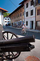 Kobarid, Julian Alps, Slovenia, July 2011. A cyclist passes the cannon in front of the Kobarid war museum. Kobarid Museum displays exhibits on the events that occurred during World War I on the Soška fronta - Isonzo Front. It covers two and a half years of static fighting and portrays in detail the 12th Isonzo battle, also known as the Caporetto breakthrough. The latter is one of the major battles in the history of mankind having taken place in hilly terrain.  Slovenia boasts a very spectacular carstic landscape with high limestone rock formations oozing with waterfalls, and fast flowing cristal clear waters that run through the Soca from the Triglav National Park to the Adriatic Sea. Photo by Frits Meyst/Adventure4ever.com