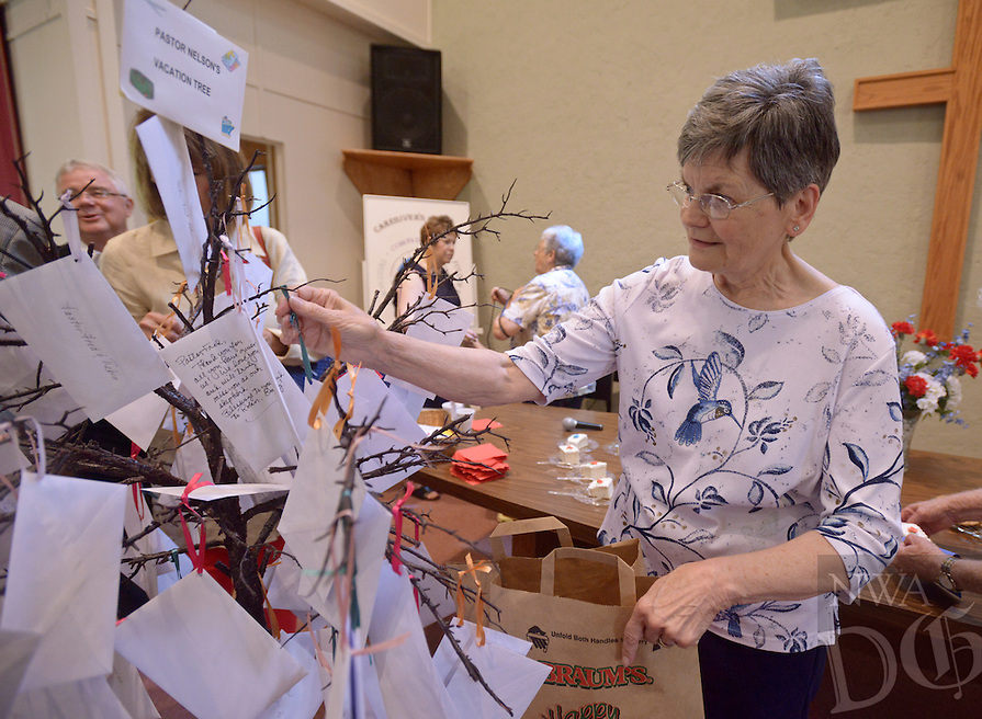 NWA Democrat-Gazette/BEN GOFF @NWABENGOFF<br /> Judy Kloss collects monetary gifts placed on a 'vacation tree' for Pastor Fred Nelson on Sunday May 29, 2016 during a retirement reception for Nelson at United Lutheran Church in Bella Vista. Nelson was the pastor of the church for over five years before stepping down in 2009 to serve as interim pastor for other congregations. Nelson served his last day in the pulpit at United Lutheran earlier in May after returning to serve as interim pastor for the congregation over the past 18 months.