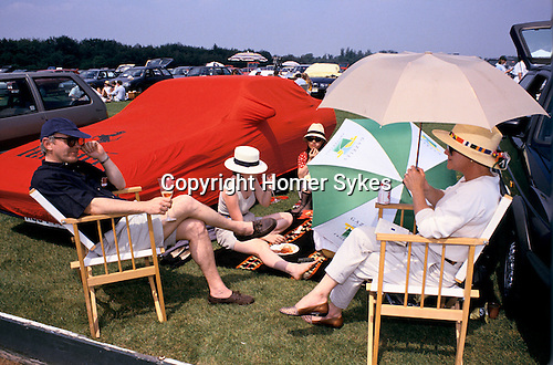 Wealthy family 1980s the car park at Windsor Great park during a Polo match, showing off their Ferrari car.