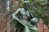 Bronze statue of The Allegory of Science, a man holding an open book and a globe, by Albert Wolff, 1814-97, with the Nikolaikirche behind, Nikolai district, Mitte, Berlin, Germany. Picture by Manuel Cohen