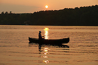 Hortonia, VT, USA - August 17, 2009: Girl fishing from a canoe as the sun sets behind tree covered hills