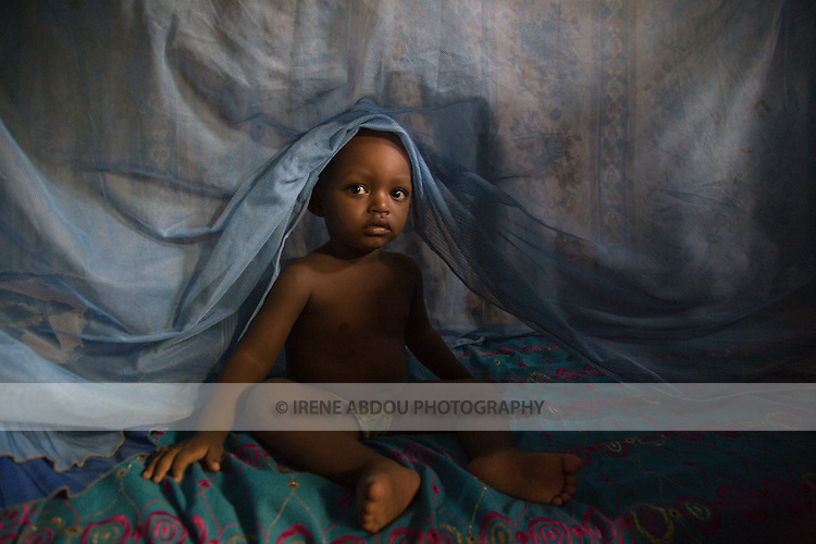 A child climbs out from under mosquito net in Kano, Nigeria.  Sleeping under a long lasting insecticide treated net every night prevents malaria.  Malaria, which is transmitted through the bite of an infected mosquito, is a major killer of children under five and pregnant women in Nigeria and the developing world.