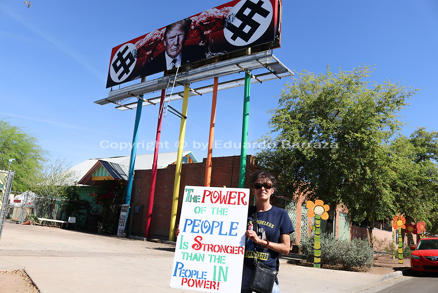"(Phoenix, Arizona) – A new billboard on top of a Phoenix building is causing controversy after the artist who created it depicts U.S. President Donald Trump surrounded by nuclear explosions and two dollar signs in the fashion of Nazi swastikas. The billboard went up on Friday, March 18, 2017 on top of the design store ""11th Monk3y Apparel and Designs."" The billboard is near Grand Avenue and 11th Avenue in Phoenix. The billboard was created by artist and activist Karen Fiorito, from Santa Monica, California. News reports indicate the billboard was commissioned by a Phoenix-based art gallery called La Melgosa. Photos by Eduardo Barraza © 2017"