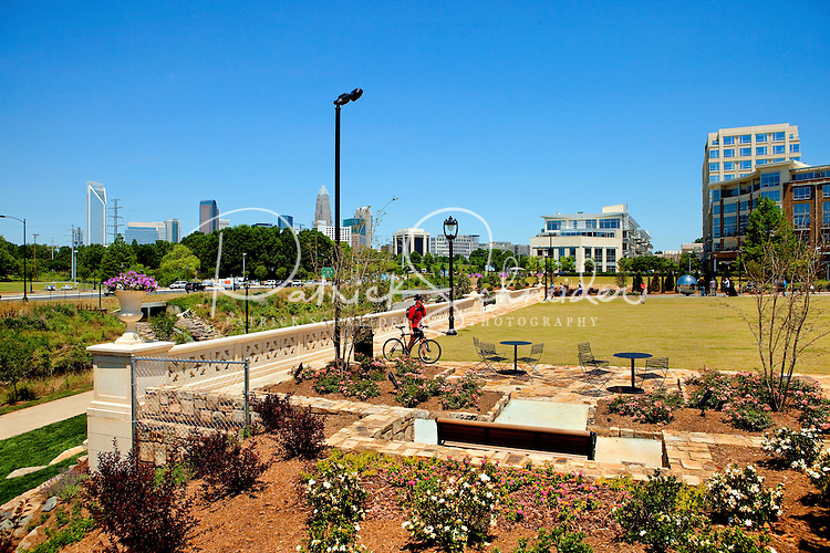 Photography of the Midtown Park area of Charlotte NC's Little Sugar Creek Greenway, a public park with more than 19 miles of trails and land connectors. Charlotte designed the Sugar Creek Greenway with the goal of connecting neighborhoods, landmarks and activities and increasing the Queen City's pedestrian-oriented activities. The Midtown Park section, located next to the Metropolitan mixed-use development, is a one-acre site that until recent years held a gas station. Today the park use of  stone, artwork and other materials brings new life to the area.