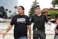 Phoenix, Arizona. April 25, 2012 - Organizer Carlos Garcia (left) of the group Puente Arizona, and a member of the Phoenix Police Department, react moments after a group of anti-SB 1070 protesters blocked a segment of Central Avenue. About 500 people protested the controversial law on the same day U.S. Supreme Court justices heard legal arguments on the Arizona vs. United States case. At the end of the march, six activists blocked Central Avenue by sitting in the middle of the street. They all were arrested by the Phoenix Police Department and taken to the Fourth Avenue County Jail. Photo by Eduardo Barraza © 2012