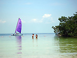 A couple wearing masks & snorkels stand in the waters of Founders Park Beach, Islamorada, Florida as a purple sailed catamaran sails by