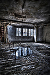 Abandoned lunatic asylum north of Berlin, Germany. Chair in empty room with water damage.