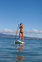 Healthy, fit woman standup paddling at Napili Bay, Maui, with Molokai in the distance.