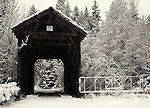 An aging wooden covered bridge serves as a gateway to unknown lands while the snow falls heavily in winter.